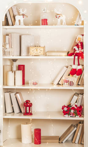 Cabinet shelves with books, candles and christmas decor