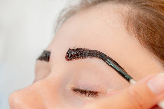 Close-up, henna staining a womans eyebrows