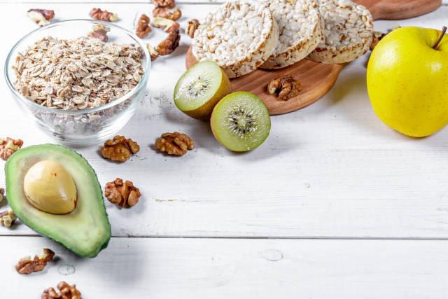 Diätkonzept mit gesundem Essen aus Haferflocken, Reiswaffeln, Nüssen, Avocado, Kiwi und Apfel