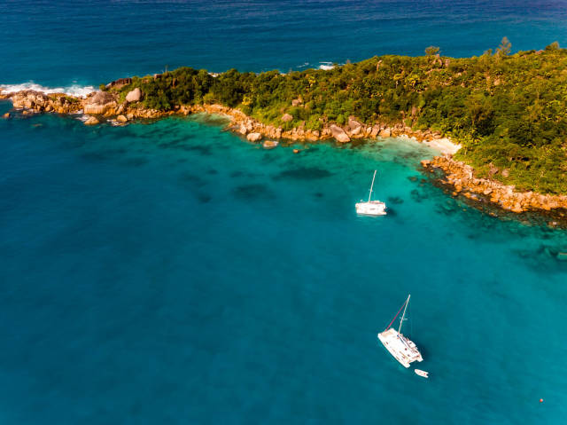 Zwei Katamaran-Boote neben einer Inselzunge an der Nordküste von Praslin, umgeben vom Tiefblauen Meer der Seychellen