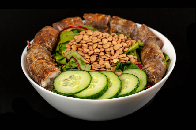 Bowl with baked sausage pieces, cucumber, chard salad and lentil