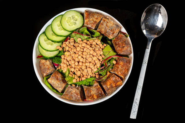 Lunch with vegetables, lentils and baked sausage on a black back