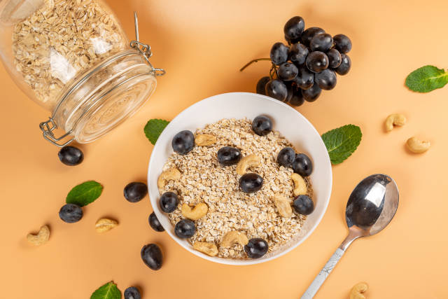 Oatmeal for breakfast with fresh blue grapes and nuts, orange ba