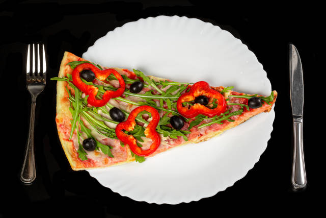 Top view, slice of pizza with arugula leaves, black olives, ham