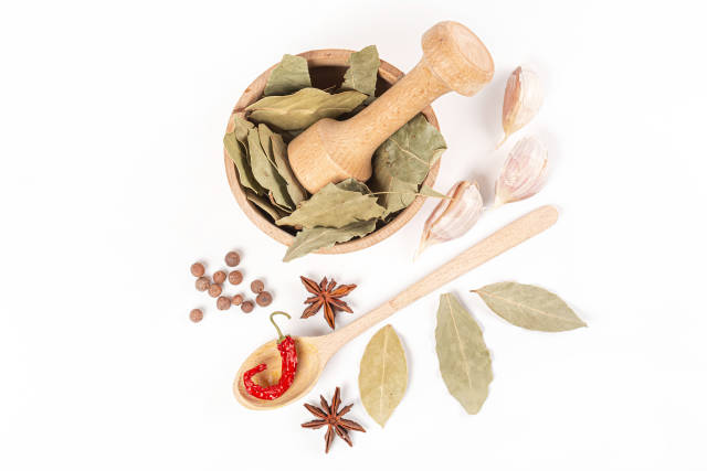 Top view, wooden mortar with bay leaves, garlic, anise, allspice