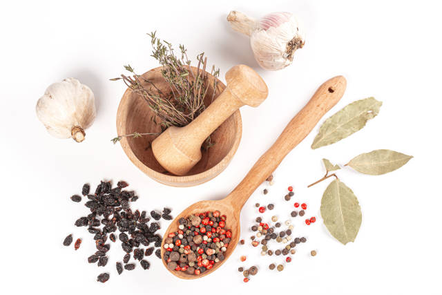 Various spices and herbs on white with wooden mortar, top view