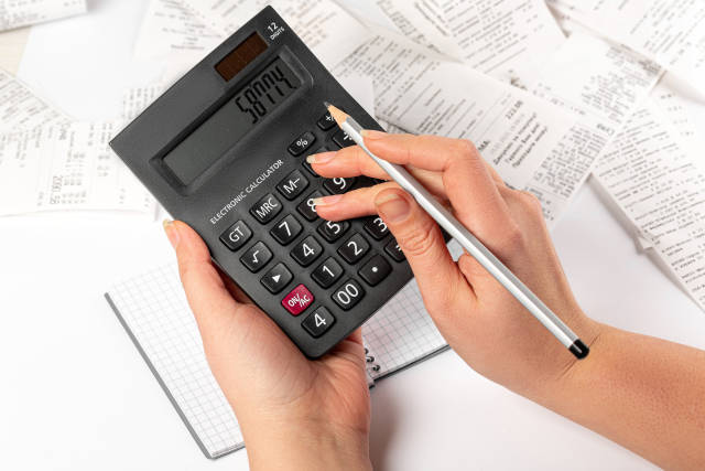 Woman using calculator to calculate bills, cost calculation conc