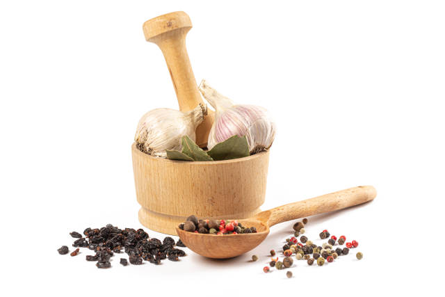 Wooden mortar and spoons with spices on white
