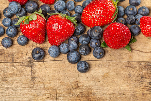 Blueberries and strawberries on an old wooden background
