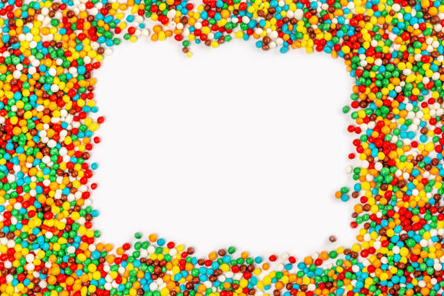 Frame made of colored easter sprinkles on a white background