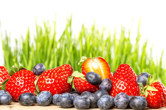 Fresh blueberries and strawberries with green grass in the backg