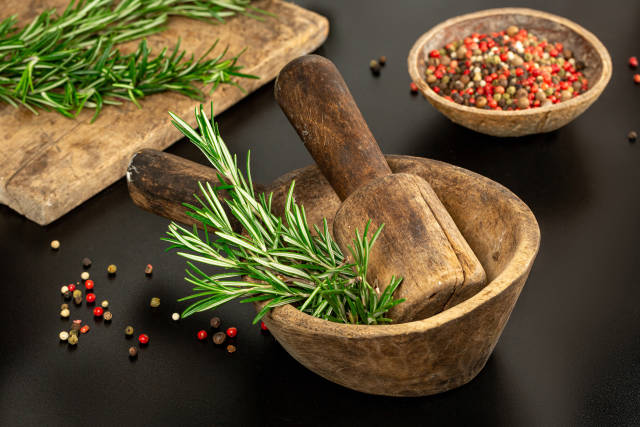 Fresh rosemary in a wooden mortar on a dark background