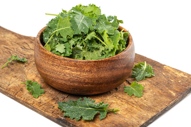 Green fresh kale cabbage leaves in wooden bowl and on old kitche