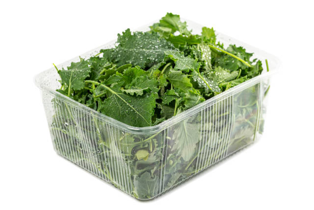 Organic leaves kales in plastic container with water drops
