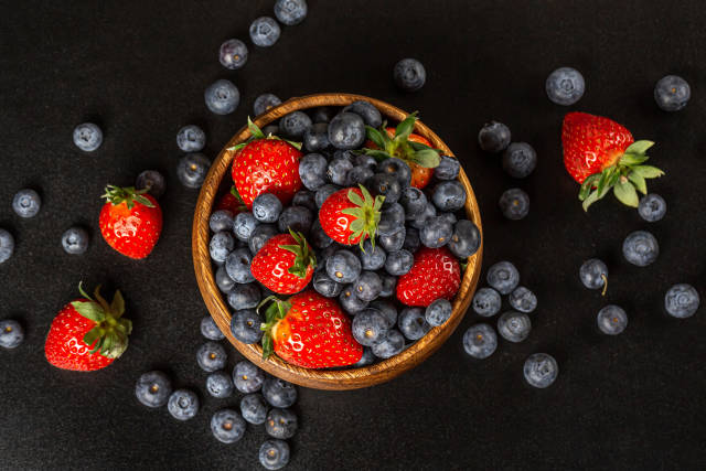 Top view, fresh ripe berries in a wooden bowl on a dark backgrou
