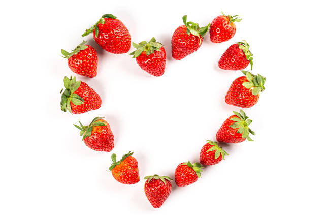 Top view, heart made of red ripe strawberries on white