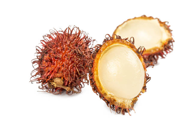 Whole and peeled rambutan on white