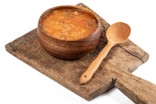 Wooden bowl of soup with rice, meat, tomatoes and pickles on an