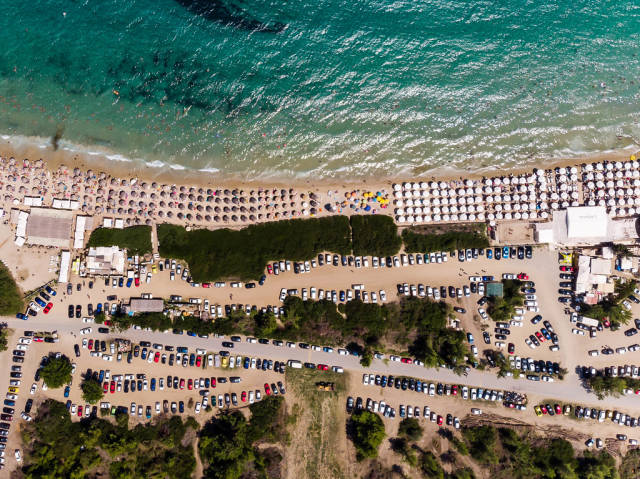 Camping site with cars and beach with parasols. Photographed from above