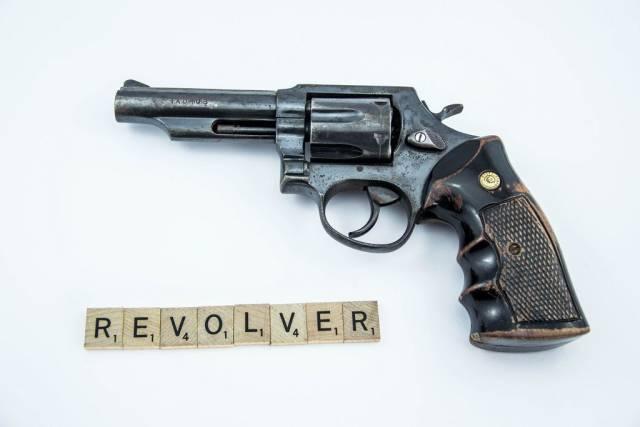 Mit Scrabble-Steinen gebildetes Wort REVOLVER vor Handfeuerwaffe auf weißem Hintergrund