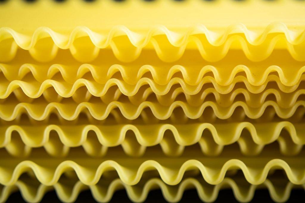 Nahaufnahme von gewellten, ungekochten, gestapelten Lasagneblättern