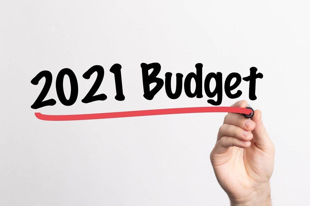 """Hand schreibt """"Budget für 2021"""" auf ein Whiteboard"""