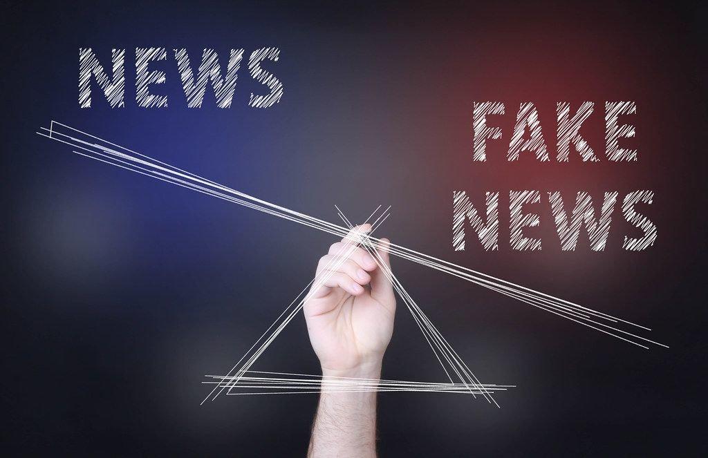 Eine Person zeichnet eine Waage unter den Wörtern News und Fake News mit Übergewicht bei Fake News