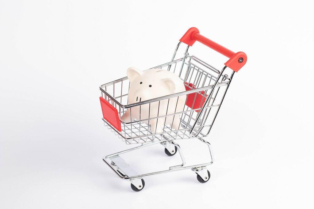 Weißes Sparschwein in Einkaufswagen symbolisiert Rabatte und Sonderangebote