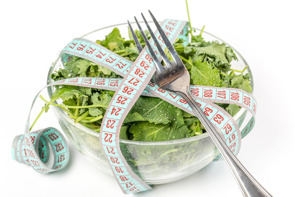 Diet salad with kale leaves, measuring tape and fork