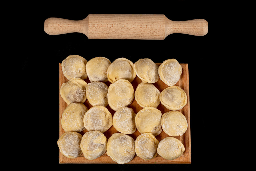 Dumplings raw on a wooden board with rolling pin, top view