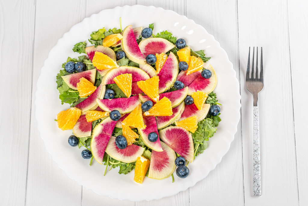 Salad with kale leaves, watermelon radish, orange and blueberry,