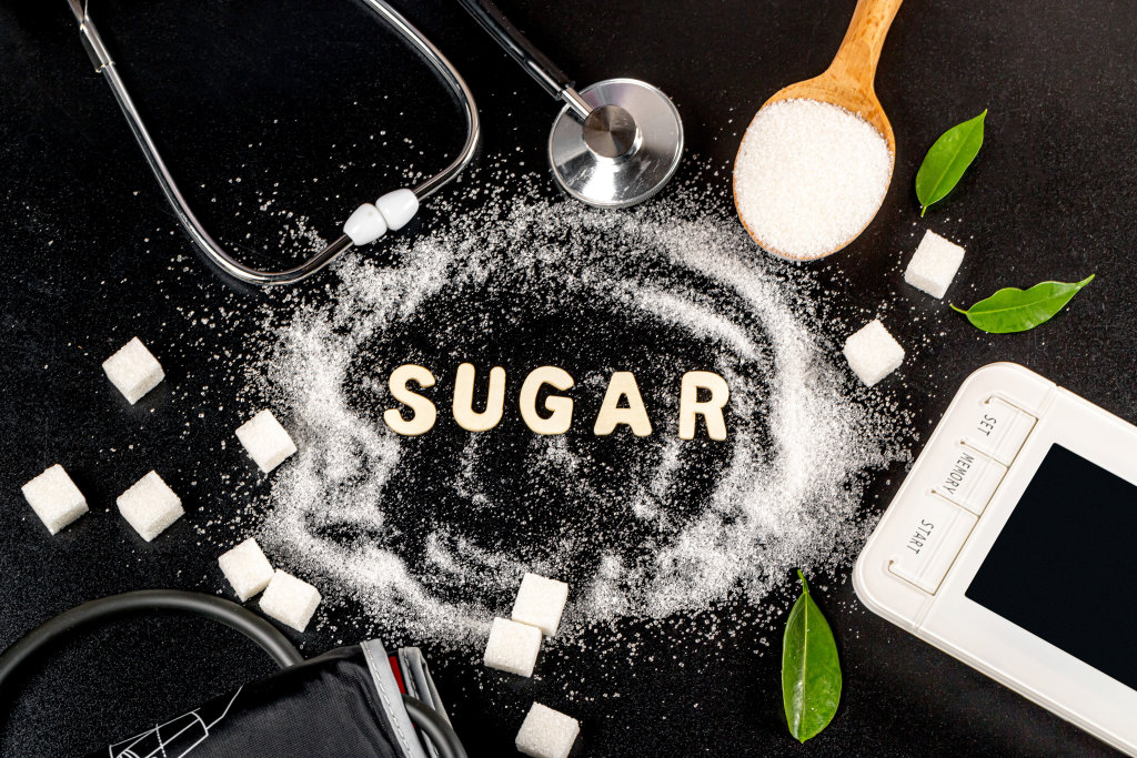 Sugar word with stethoscope, tonometer and sugar cubes on dark b