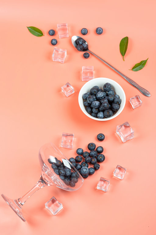 Top view of blueberries with ice cubes and glass on pink backdro