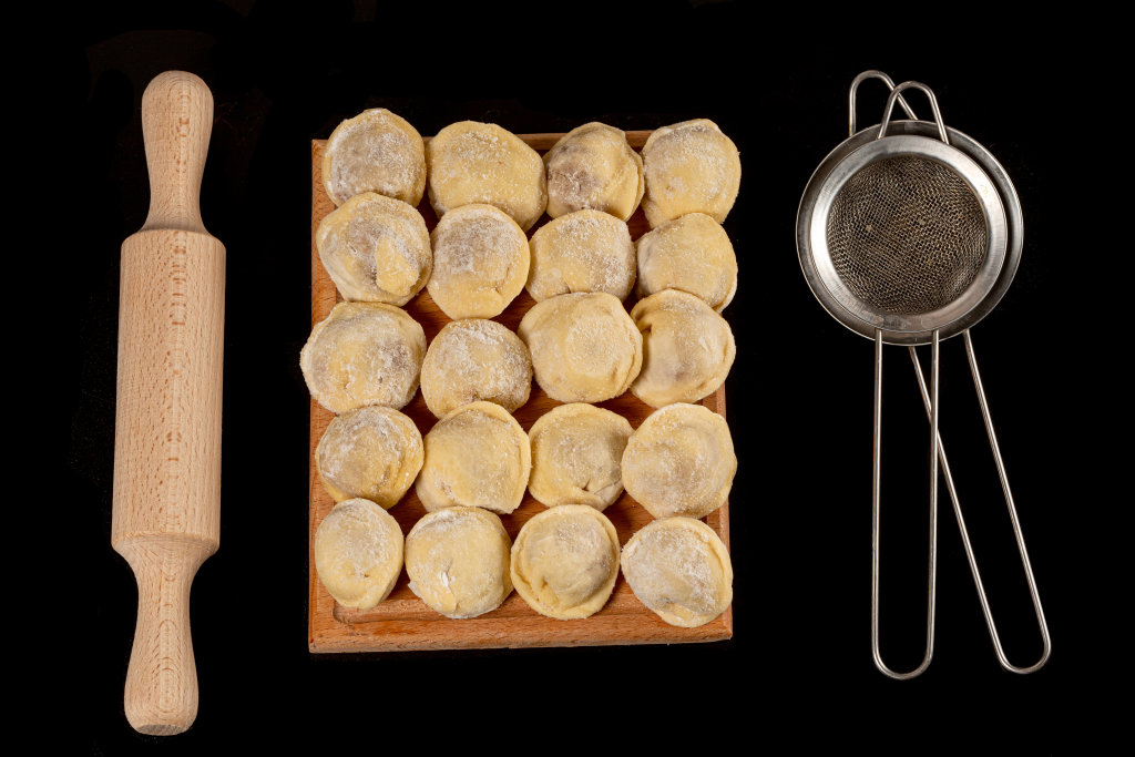 Top view of raw homemade dumplings on black background with roll