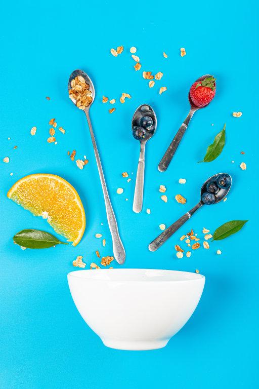 White bowl with breakfast ingredients in teaspoons on blue backg