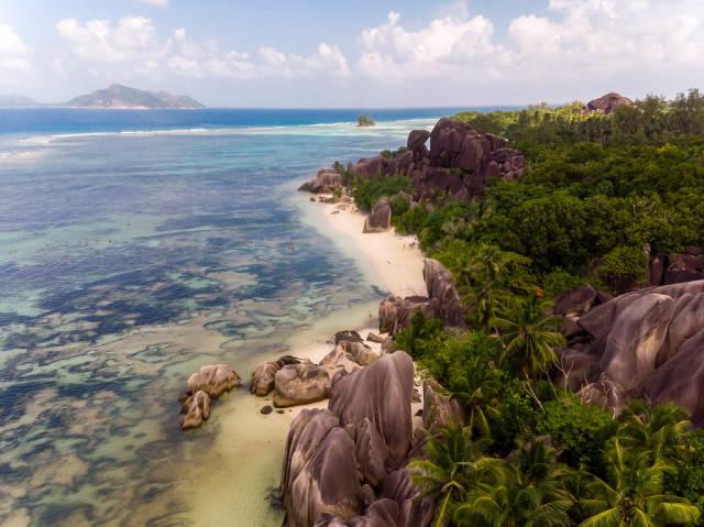 Luftbild zeigt Palmen, Granitfelsen und den Strand Anse Source dArgent auf der Seychelleninsel La Digue mit badenden Menschen im Indischen Ozean