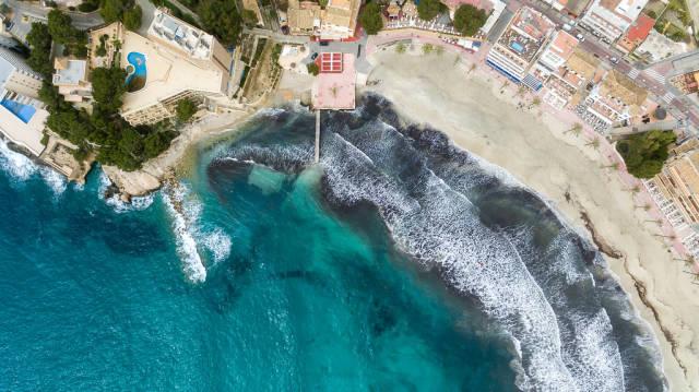 Strand und kleiner Bootssteg in Peguera, Mallorca aus der Vogelperspektive