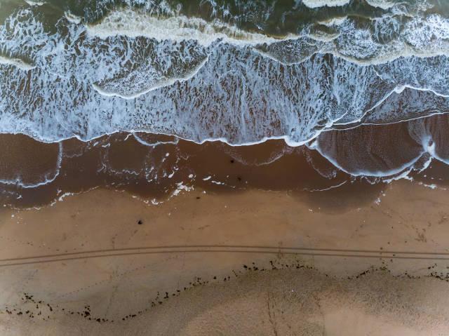 Drohnenaufnahme Sandstrand mit hereinrollenden Wellen