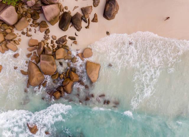 Luftaufnahme des Anse Lazio Strands im Norden von Praslin (Seychellen), mit türkisblauem Meer und Granitsteinen