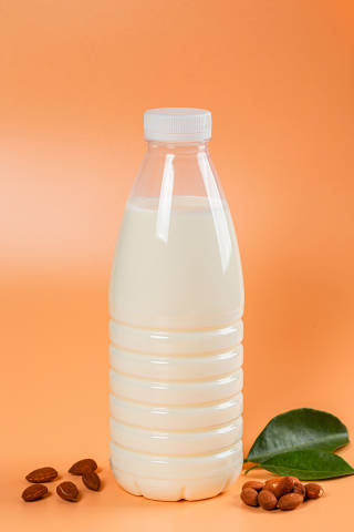 Milk bottle on orange background with almonds