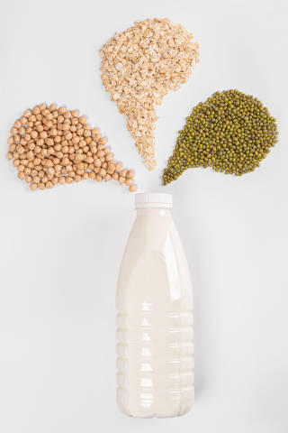 Milk bottle with oatmeal, chickpeas and mung beans on white back