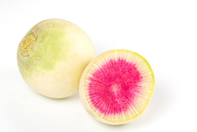 One whole and half watermelon radish on a white background