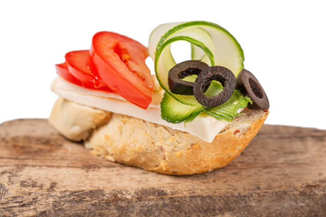 Sandwich with cheese, slices of tomato, cucumber and black olive