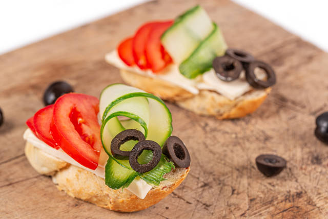Sandwich with sliced tomato, cucumber, olives and cheese on a wo
