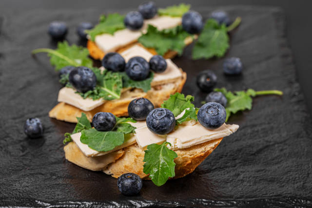 Sandwiches with cheese, blueberries and kale leaves