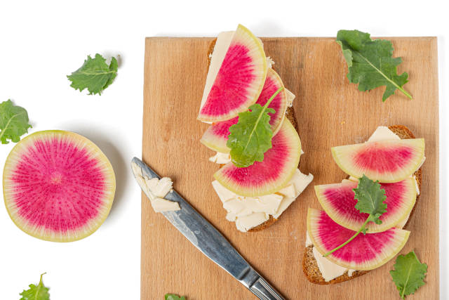 Sandwiches with cheese, watermelon radish and kale leaves on kit