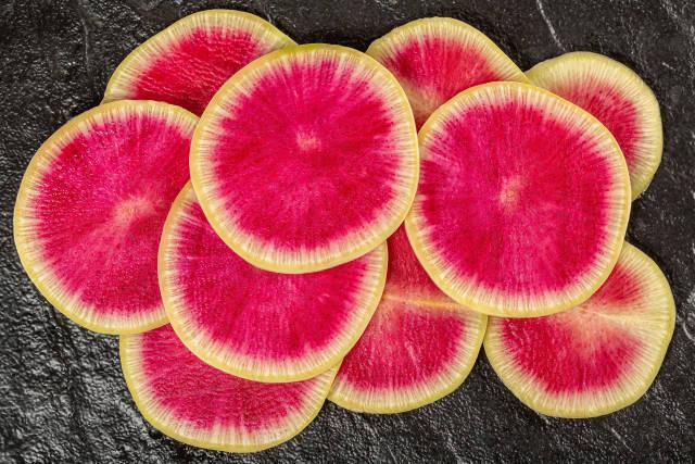 Sliced watermelon radish on black background, top view