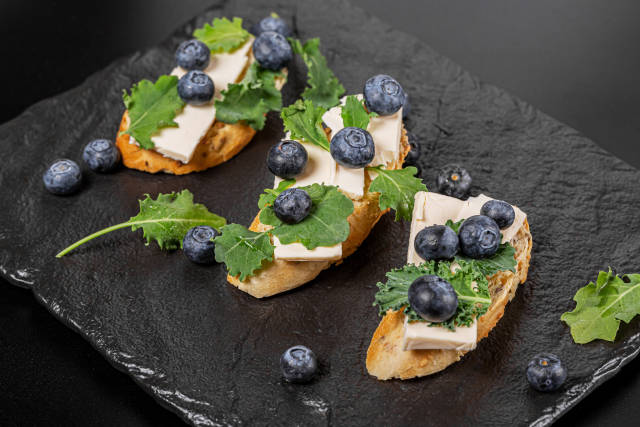 Three sandwiches with cheese and fresh blueberries