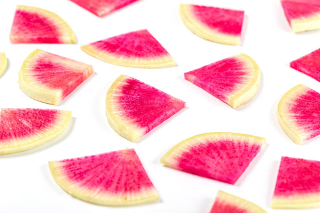 Watermelon radish slices, yellow pink pieces on white background