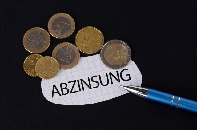 Das Konzept von Abzinsung: Abzinsung Text auf einem Blatt Papier mit einigen Münzen und einem blauen Stift im schwarzen Hintergrund